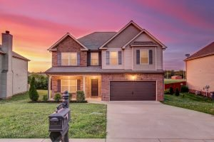 Two story brick home with black mailbox and sunset pink and yellow sky in background