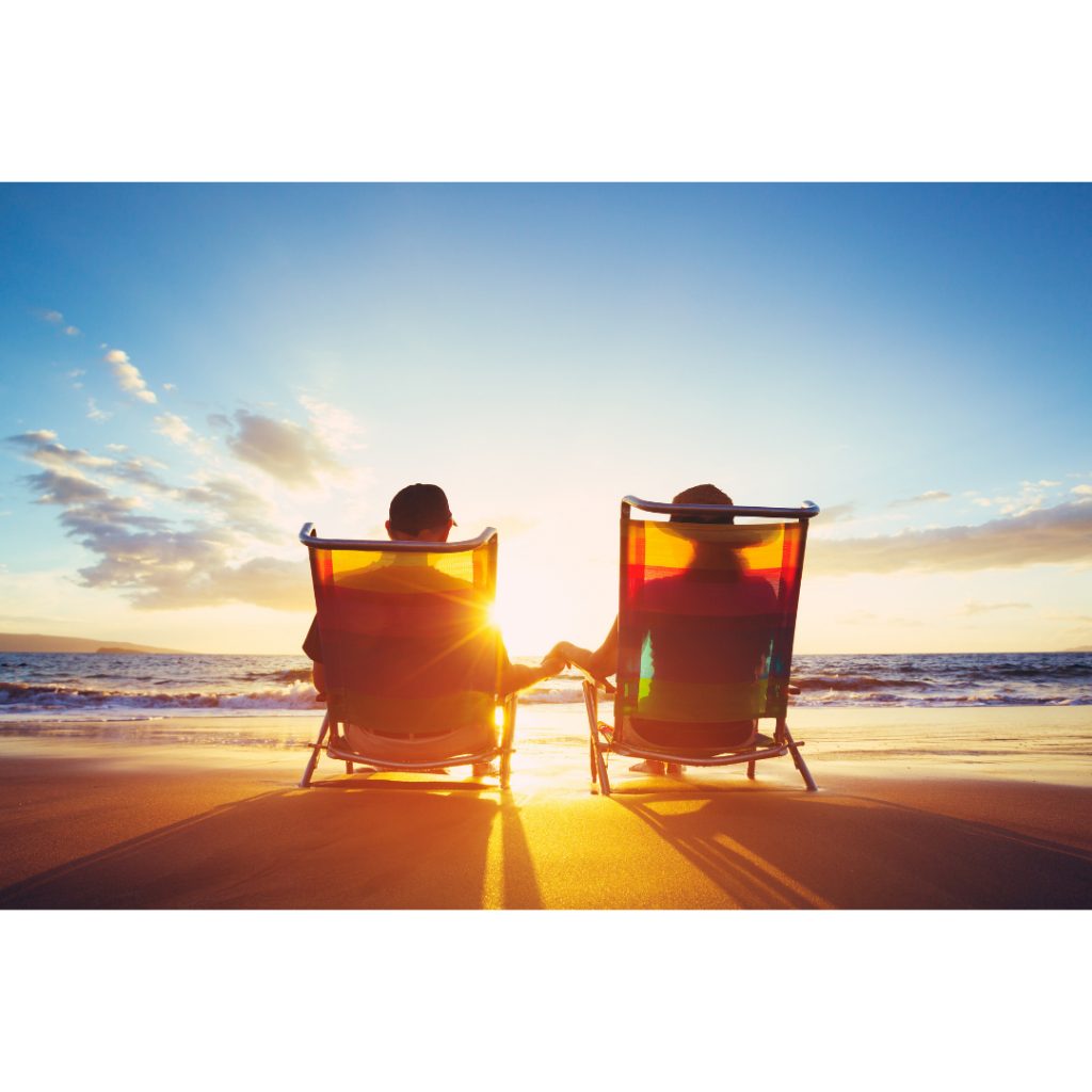 Couple on beach in lounge chairs, holding hands during sunset - vacation paid for by reward points from building credit